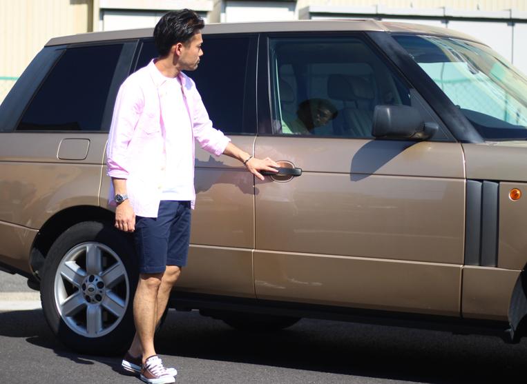 車の前でピンクシャツにネイビーのショートパンツを来た男性