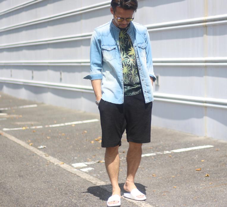 デニムシャツにパイルのショートパンツを履いた男性