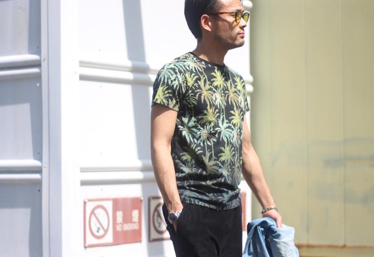 ボタニカル柄の半袖Tシャツを着た男性