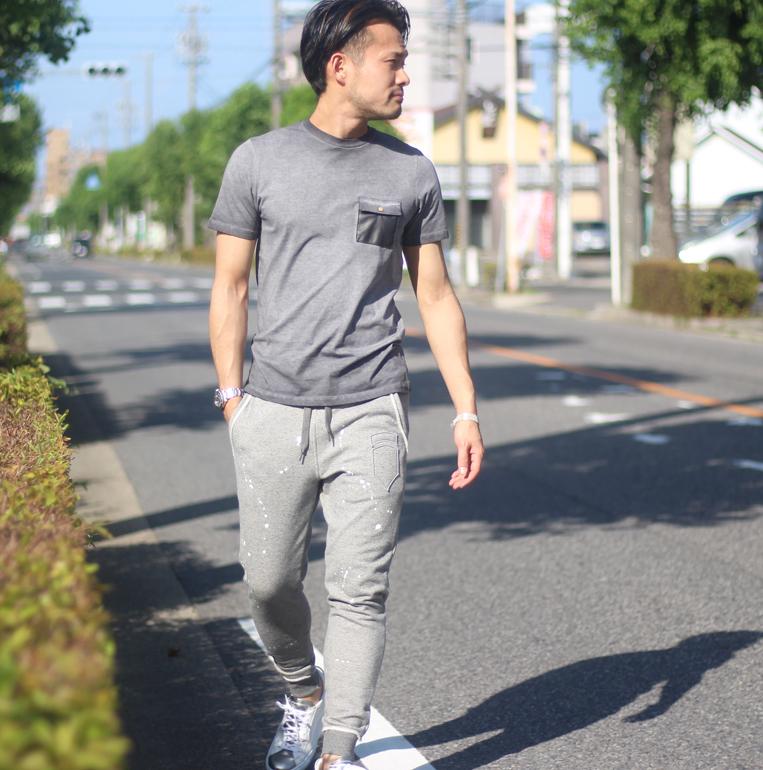 グレーの半袖Tシャツにスウェットパンツを着た男性