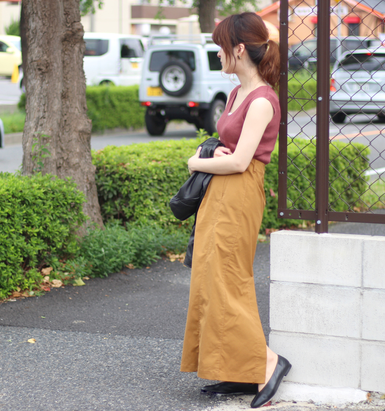ニットノースリーブにロングタイトスカートを着た女性