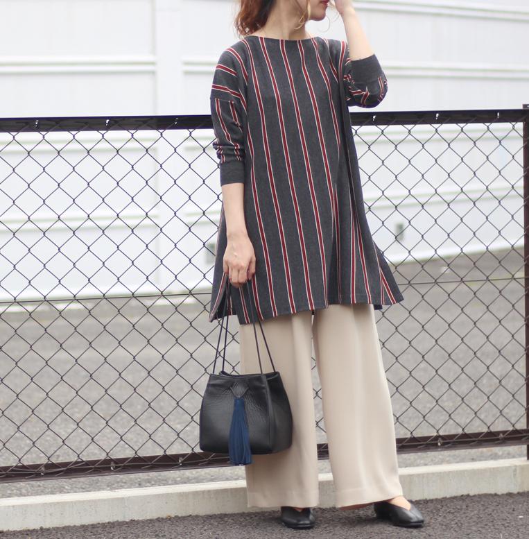 ストライプロングニットにワイドパンツを着た女性