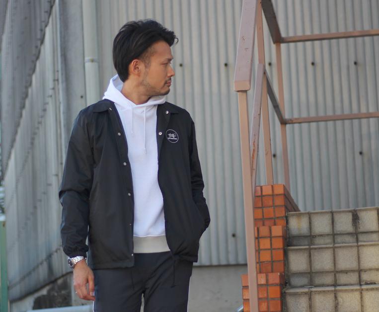 コーチジャケットにプルオーバーパーカーを着た男性