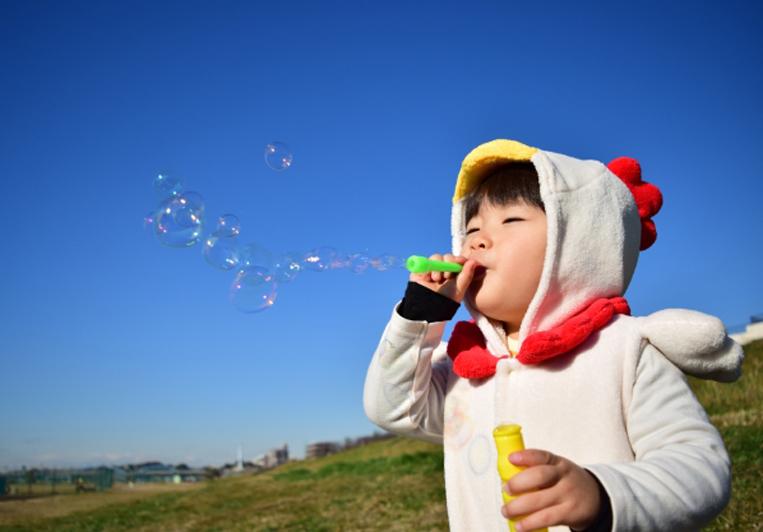 着ぐるみを着てシャボン玉をする子供の写真