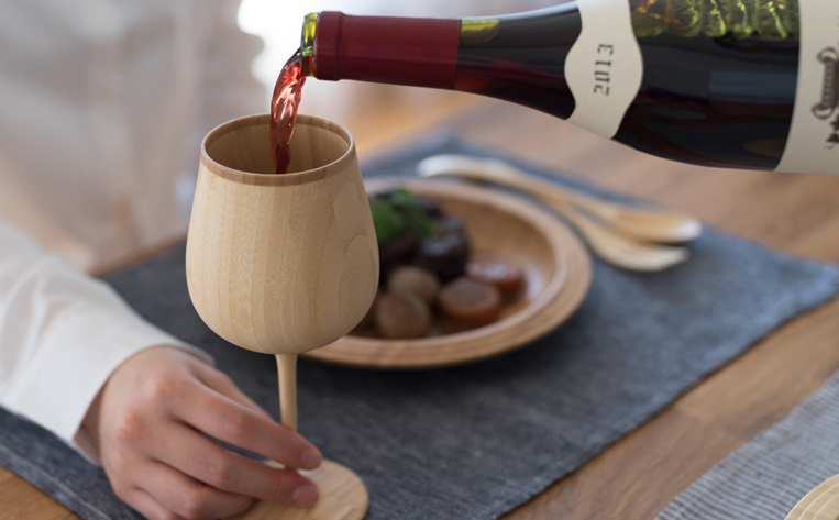 竹でできたワイングラスにワインを注ぐ様子