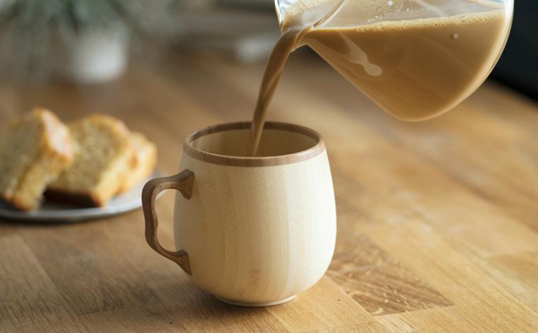 竹でできたマグカップにカフェオレを注ぐ様子