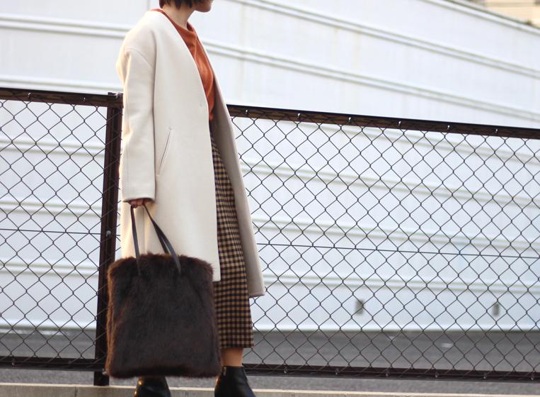 アイボリーのノーカラーコートにチェックスカートを着た女性