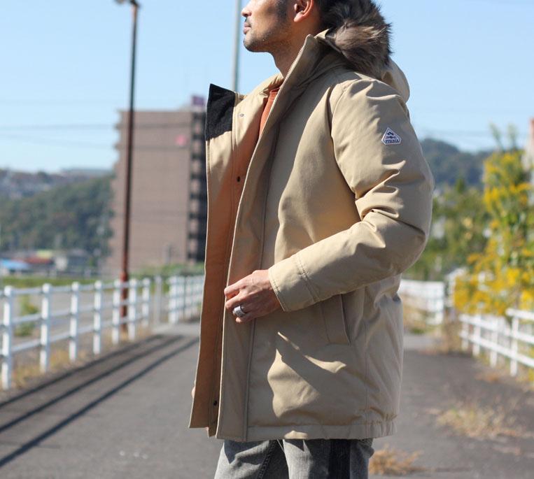 ピレネックスのベージュのダウンジャケットを着た男性