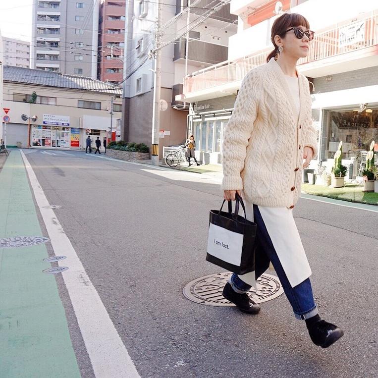 モノトーンのレザーバッグを持って歩く女性