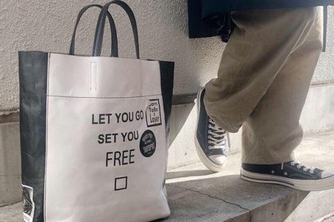 モノトーンのレザーバッグを足元に置いた男性
