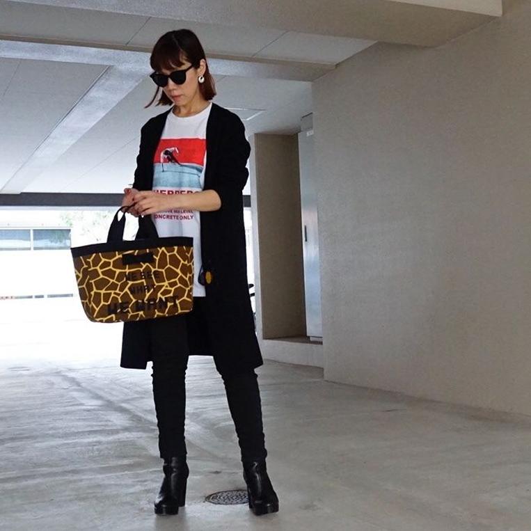 モノトーンコーデにキリン柄バッグを合わせた女性
