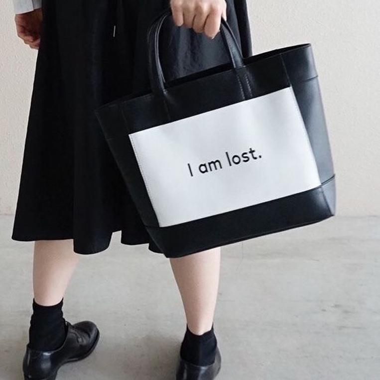 モノトーンのレザーバッグを持った女性