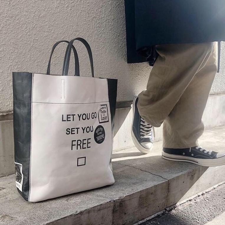 男性の足元に置かれたモノトーンのレザーバッグ