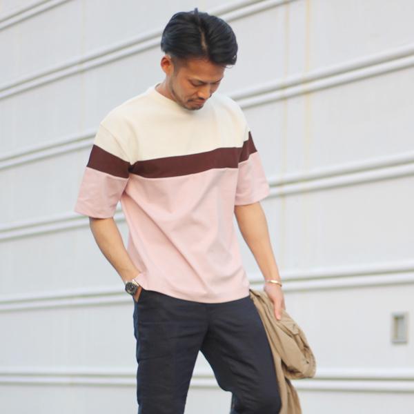 ホワイト×ブラウン×ピンクのマルチカラーニットを着た男性