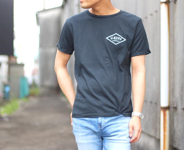 ワンポイントロゴが入ったブラックの半袖Tシャツを着た男性