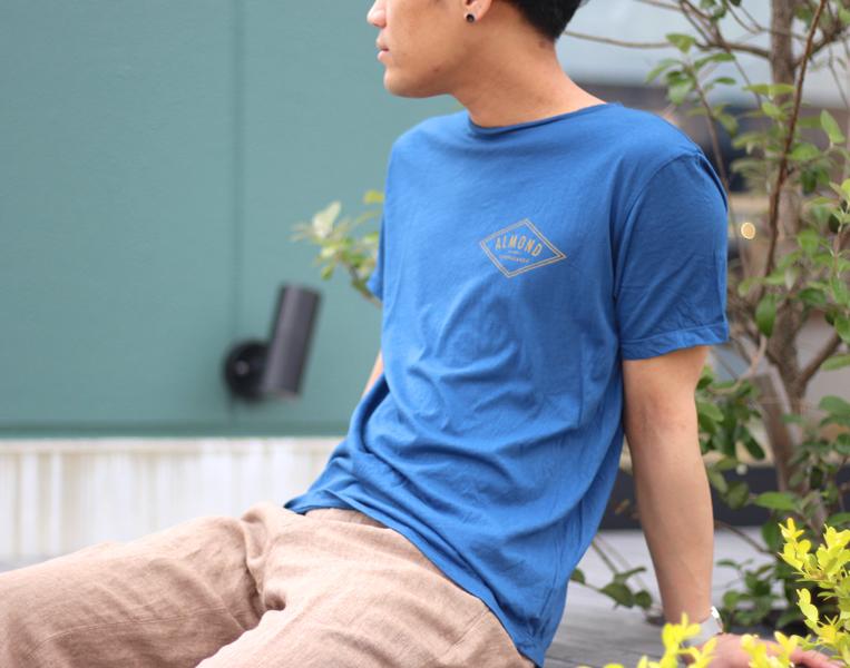 ワンポイントロゴが入ったブルーの半袖Tシャツを着た男性