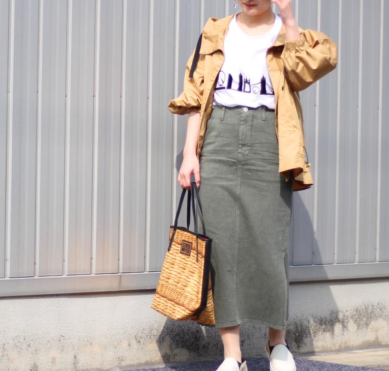ベージュのマウンテンパーカーにタイトスカートの着た女性