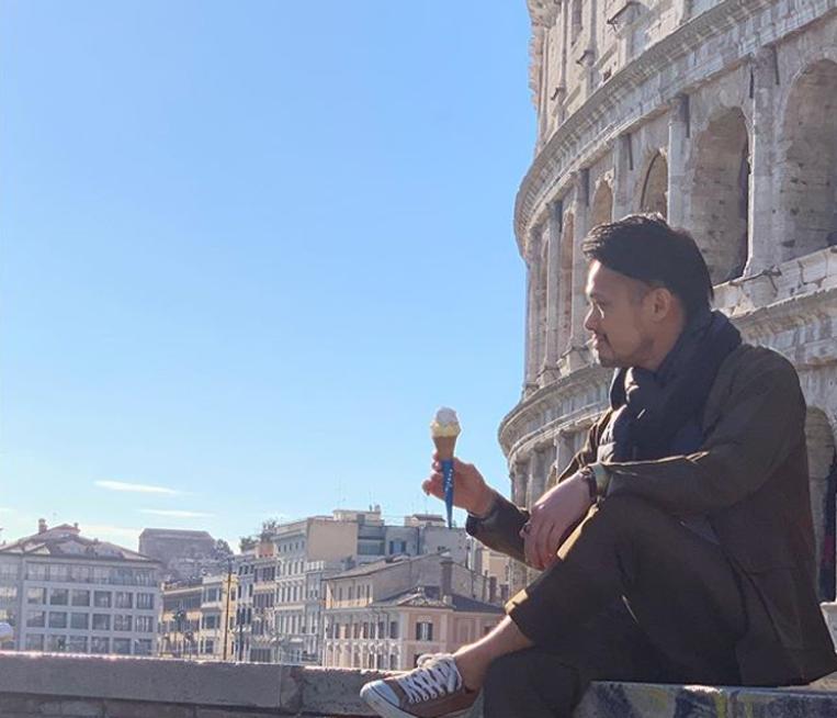 ローマの街中でジェラートを食べる男性
