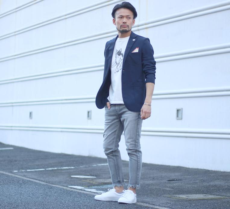 ネイビーのテーラードジャケットにプリントTシャツを着た男性
