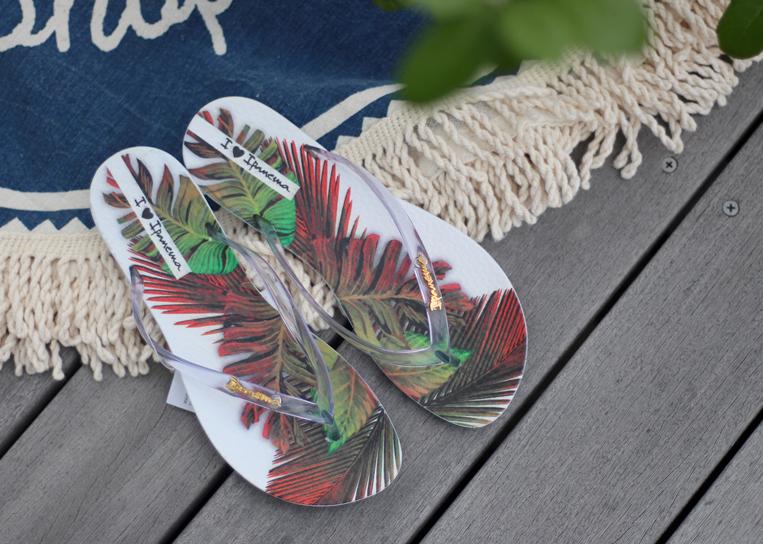 ウッドデッキに置かれたボタニカル柄のビーチサンダル