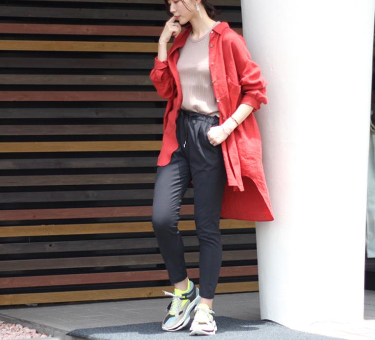 赤のロングリネンシャツを着た女性