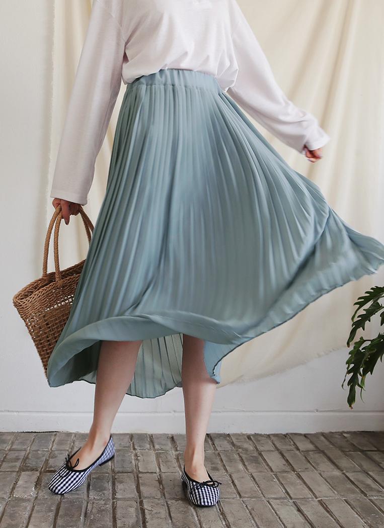 ミントグリーンのプリーツスカートを穿いた女性