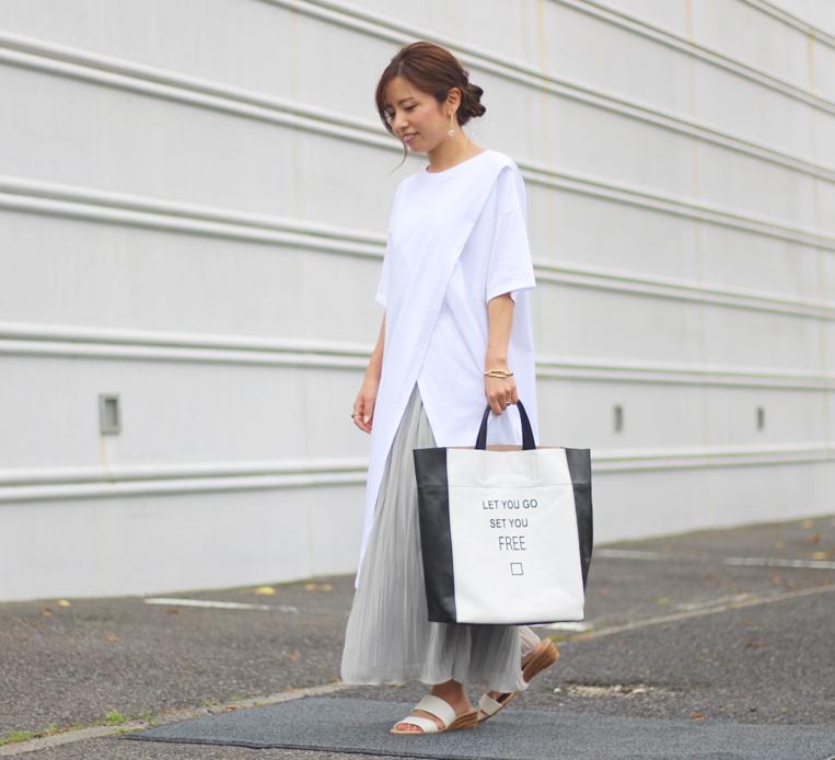 白いチュニックにプリーツスカートを合わせた女性