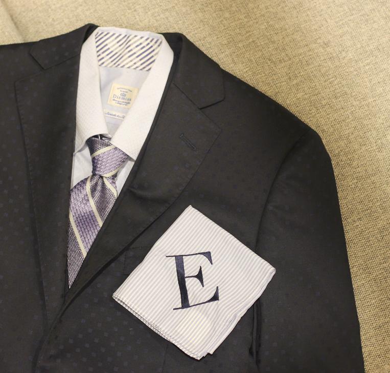 スーツの上に置かれたEのイニシャルハンカチ