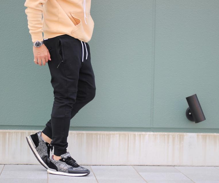 ブラックのスウェットジョガーパンツを穿いた男性