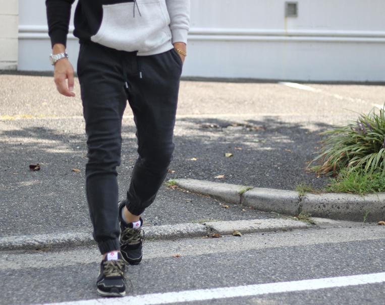 ブラックのデニムジョガーパンツを穿いた男性