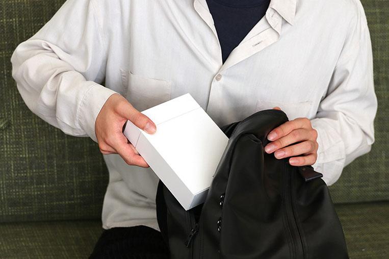 加湿器をバッグに入れる男性