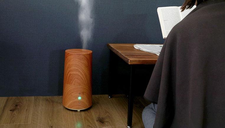 テーブルの隣に置かれたウッド調のアロマ加湿器