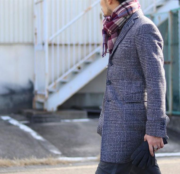 千鳥格子柄のチェスターコートを着た男性