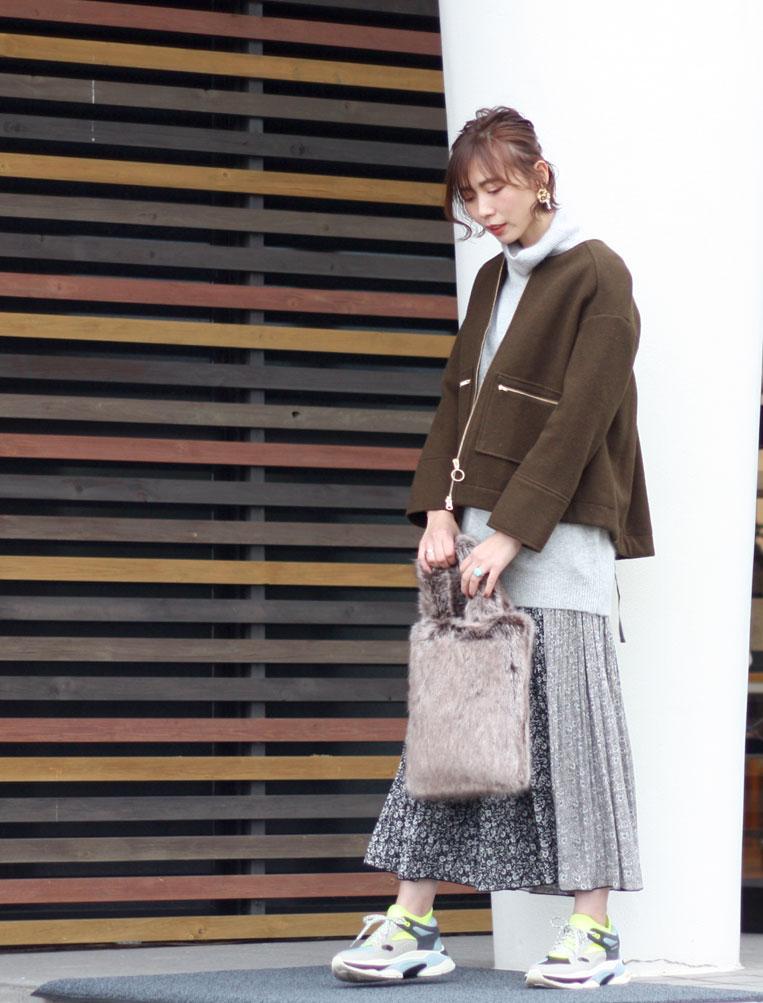ミドル丈ニットにショート丈ブルゾンを羽織った女性