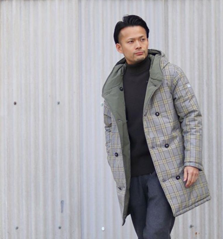 グレーのチェックコートを羽織った男性