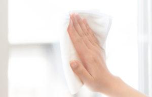 雑巾でガラスを拭く人