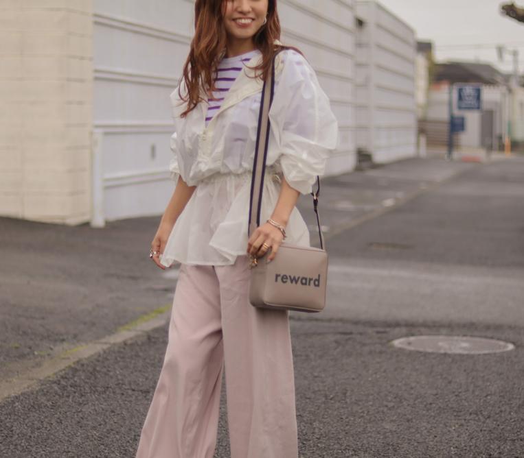 くすみピンクのワイドパンツを穿いた女性