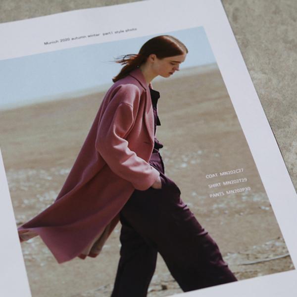 くすみピンクのコートを着た女性