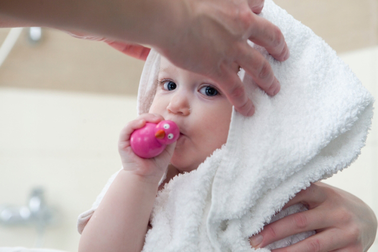 タオルで体を拭かれている赤ちゃん