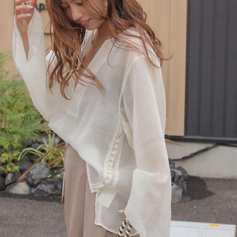 シアー素材のブラウスを着た女性