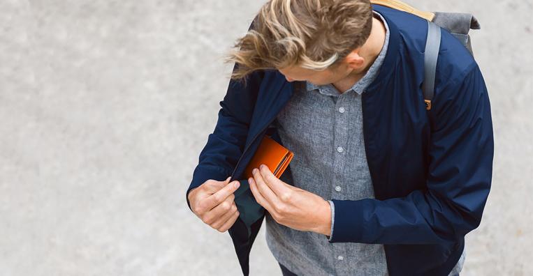 ミニ財布をポケットに入れている男性