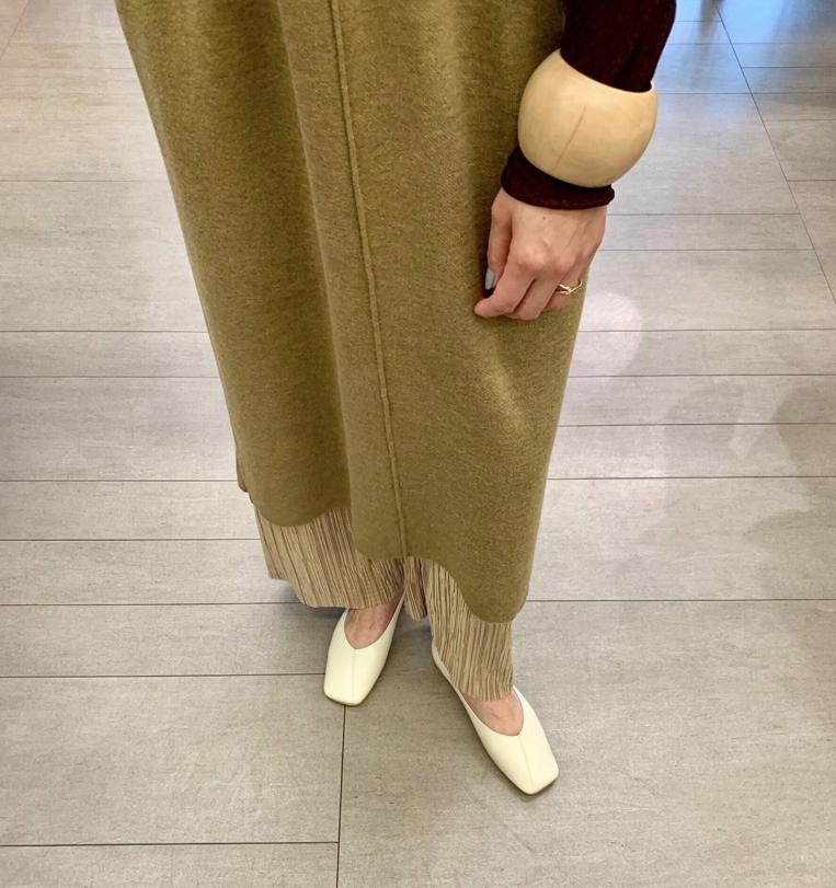アイボリーのスクエアトゥパンプスを履いた女性