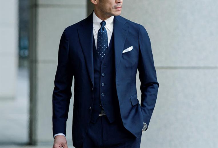 濃紺の無地スーツを着た男性